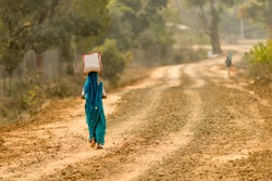 A woman in rural India carrying a bag on her head.