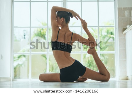 A woman in shorts a short T-shirt in front of the window is practicing yoga asana            #1416208166