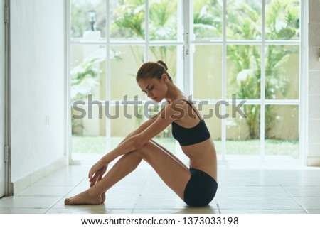 A woman in shorts and a short vest sits on the floor near the window of yoga asana meditation                      #1373033198