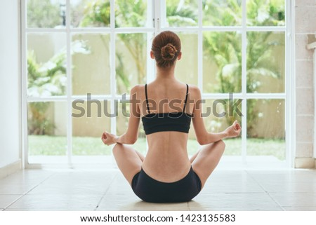 A woman in shorts and a t-shirt is meditating in front of the window from behind                #1423135583