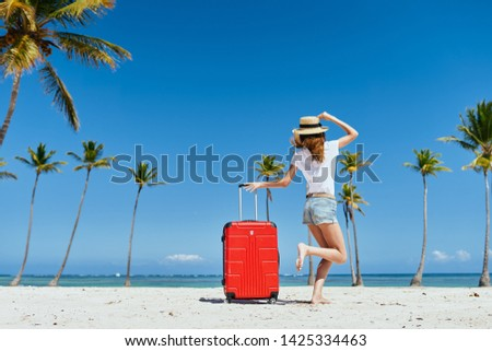 A woman in shorts and a t-shirt leaned on the handle of a suitcase and stands on the sand with a hat on her head                        #1425334463