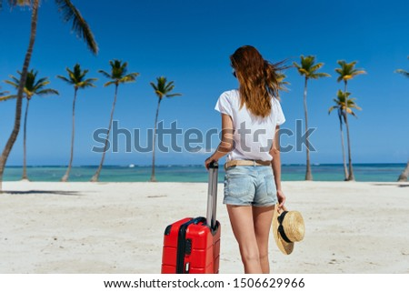 A woman in shorts and a T-shirt with a suitcase in hand is walking on the sand on the island                              #1506629966