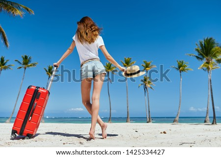 A woman in shorts with a red suitcase stands barefoot on an island with palm trees and a straw hat                        #1425334427