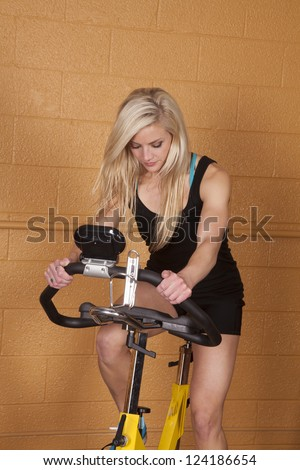 A woman in the gym exercising on a bike.