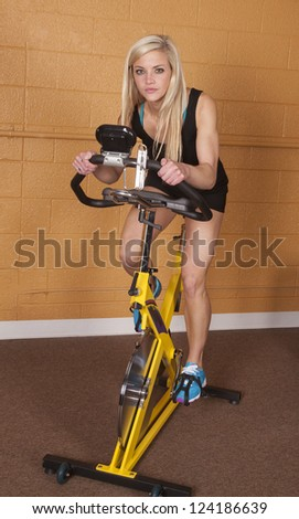 A woman in the gym riding an exercise bike with a serious expression on her face.
