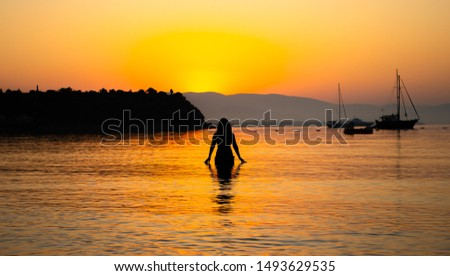 A woman in the sea and the view of sunrise #1493629535