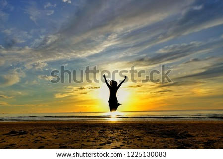 A woman in the shadow jumping on the beach in the morning backlit. Silhouette image.