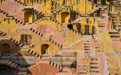 A woman in traditional dress visit the ancient Indian deep well with lots of steps in Jaipur, India.