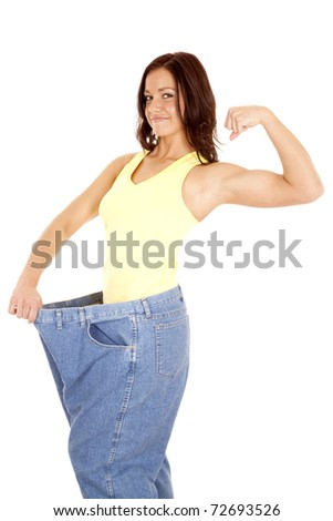 A woman in very large pants and a small waist is showing her muscles.