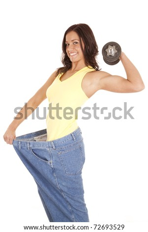 A woman in very large pants is holding a weight up with one arm