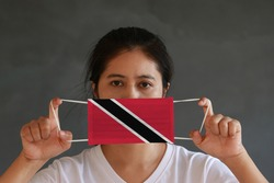 A woman in white shirt with Trinidad and Tobago flag on hygienic mask in her hand and lifted up the front face on dark grey background. Tiny Particle or virus corona or Covid 19 protection.