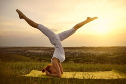 A woman in white sportswear is practicing yoga balsa standing on her head on the grass outdoors outdoors at sunset.
