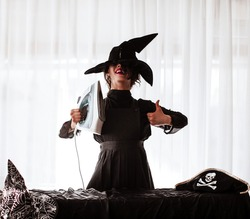 A woman is a housewife dressed in black clothes and a large Halloween hat on her head holding an iron in her hands to iron outfits for the holiday. Funny girl shows her finger that she likes iron.