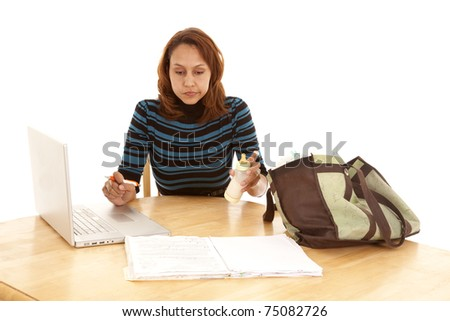 A woman is at a table trying to work and be a mom.