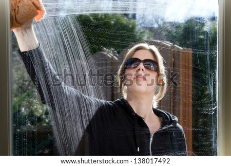 A woman is cleaning a window of her house