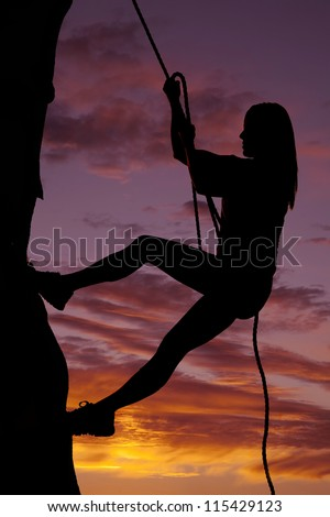 A woman is climbing a rock wall in the sunset.