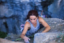 A woman is climbing in Turkey, Turkish woman climbs the rock, Extreme hobby, Overcoming a difficult climbing route, Overcoming the fear of heights, Climbing effort.