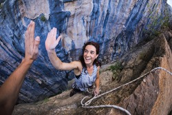 A woman is climbing in Turkey, Turkish woman climbs the rock, Extreme hobby, Overcoming a difficult climbing route, Overcoming the fear of heights, Emotional girl gives five to a friend.