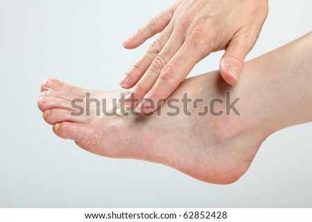 A woman is creaming and massaging her feet