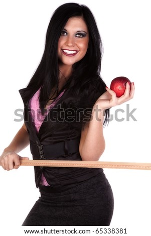 A woman is dressed like a teacher with a ruler in one hand and an apple in the other.