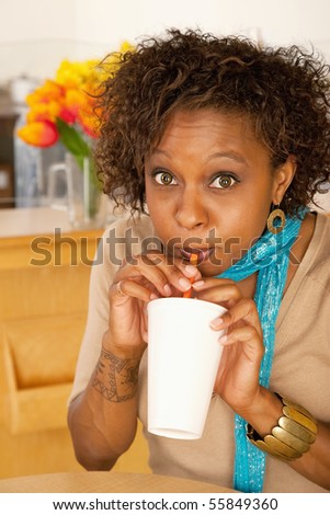 A woman is drinking a beverage from a cup and looking at the camera.  Vertical shot.