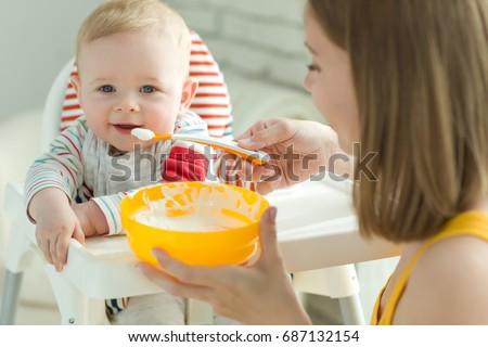 A woman is feeding a child