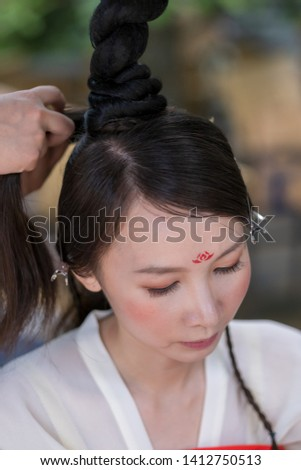 A woman is having her long hair braided before an opera show.