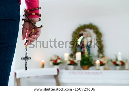 A woman is holding a chain with the cross in front of a Maria statue in a chapel - stock photo