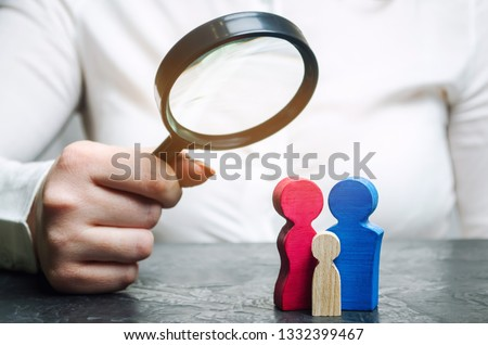 A woman is holding a magnifying glass over the wooden figures. Studying family composition, needs and health. Popularization of family creation. Demographic policy. Gene research. Family tree