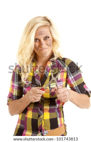 A woman is holding a pair of pliers with a serious look on her face.
