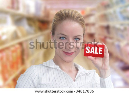 A woman is holding up a red card that has the word SALE on it. She looks happy and is standing in a department store.