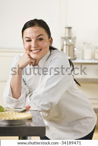 A woman is in a kitchen and baking a pie.  She is smiling at the camera and her face is covered in flour.  Vertically framed shot.