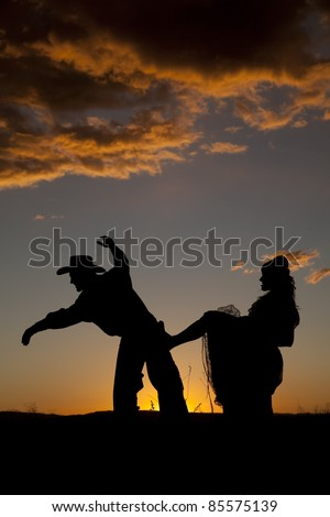 A woman is kicking a cowboy in the butt in the sunset.