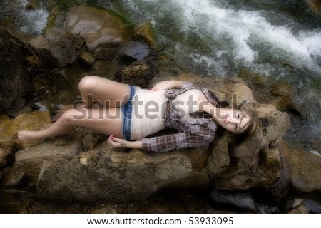 A woman is laying on her back on a big rock with the river for Laying river rock