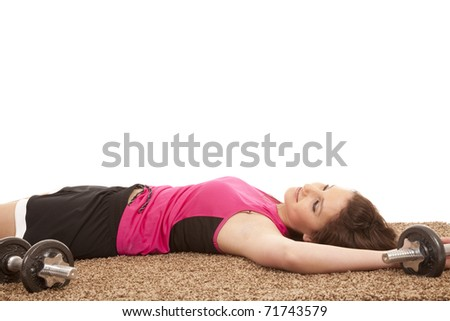 A woman is laying on the floor with weights exhausted.