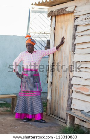 A woman is leaning in front of her home.