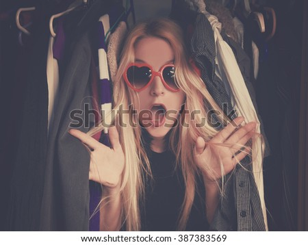 A woman is overwhelmed in a closet of messy clothes with red glasses for a style or fashion concept. #387383569