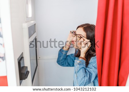 A woman is photographed and amused in a photo booth, making istant selfie photos for fun or for passport and documents #1043212102