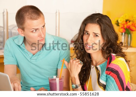 A woman is pointing to a man and making a disgusted face.  Horizontal shot.