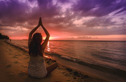 A woman is practicing yoga on the beach when it is sunset