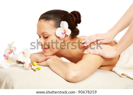 A woman is relaxing during a massage isolated on white background