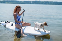 A woman is riding a surfboard with a dog