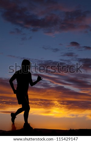A woman is silhouetted in the sunset and running.
