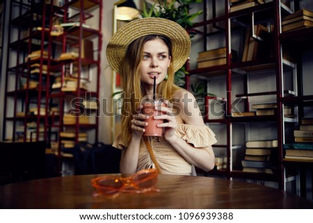 A woman is sitting at a table and drinking a cocktail                           #1096939388