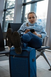 A woman is sitting at the airport with her feet on a suitcase, and in advance, before boarding the plane, puts her smartphone in the