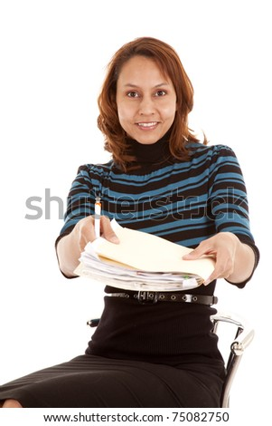 A woman is sitting handing over a folder of papers.