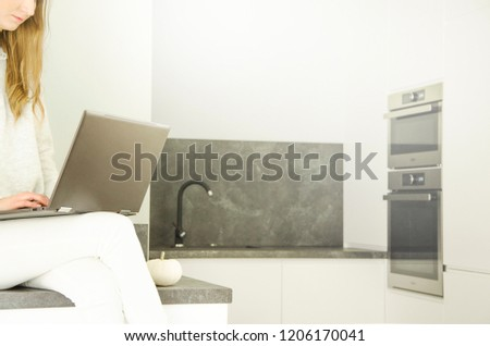 A woman is sitting in a modern kitchen with a laptop. #1206170041