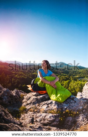 A woman is sitting in a sleeping bag at sunset. Travel to picturesque places. Camping on top of a mountain. A smiling girl rests after a climb. The brunette sits on the background of the sky. #1339524770
