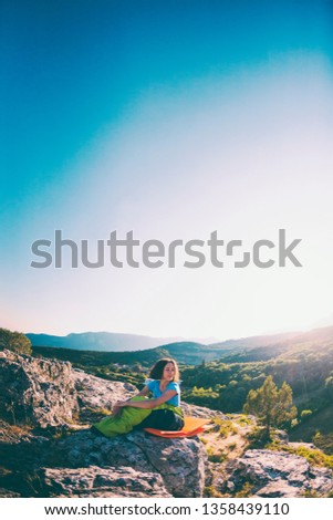 A woman is sitting in a sleeping bag at sunset. Travel to picturesque places. Camping on top of a mountain. A smiling girl rests after a climb. The brunette sits on the background of the sky. #1358439110