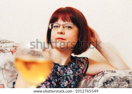 A woman is sitting in front of a glass of wine #1012765549